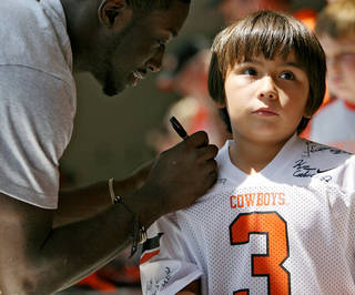 OSU / OKLAHOMA STATE UNIVERSITY / COLLEGE FOOTBALL: OSU player Larry Stephenson (left) signs a shirt for Jaden Ybarra, 8, of Edmond, during Oklahoma State's Fan Appreciation Day at Gallagher-Iba Arena in Stillwater, Oklahoma on Saturday, Aug. 6, 2011. Photo by John Clanton, The Oklahoman ORG XMIT: KOD