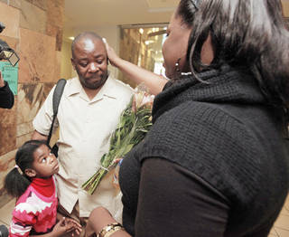 Humphreys Munai, center, is greeted Thursday by his wife, Judith, and daughter, Imani, 5, after arriving at Will Rogers World Airport in Oklahoma City. Photo by Nate Billings, The Oklahoman
