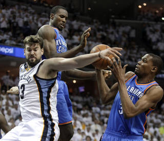 Memphis Grizzlies center Marc Gasol (33), of Spain, fights for a rebound with Oklahoma City Thunder forward Serge Ibaka, center, and Kevin Durant during the second half of Game 3 of a second-round NBA basketball series on Saturday, May 7, 2011, in Memphis, Tenn. The Grizzlies won 101-93 in overtime to take a 2-1 lead in the series. (AP Photo/Lance Murphey)