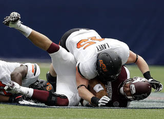 Oklahoma State's Caleb Lavey (45) helps bring down Mississippi State's Tyler Russell (17) as Oklahoma State's Shaun Lewis (11) pulls him down for a sack during first half of the AdvoCare Texas Kickoff college football game between the Oklahoma State University Cowboys (OSU) and the Mississippi State University Bulldogs (MSU) at Reliant Stadium in Houston, Saturday, Aug. 31, 2013. Photo by Sarah Phipps, The Oklahoman