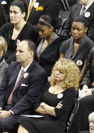 Oklahoma women's basketball coach Sherri Coale, right, sits with Oklahoma athletic director Joe Castiglione, left, and members of her team, at rear, during a memorial service in Stillwater, Okla., Monday, Nov. 21, 2011. Oklahoma State women's basketball Kurt Budke and assistant women's basketball coach Miranda Serna were killed along with pilot Orlin Branstetter and his wife, Paula Branstetter, in a plane crash last Thursday. (AP Photo/Sue Ogrocki) ORG XMIT: OKSO119