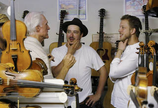 In this Sept. 5, 2013, photo Marcus Mumford, center, and Ted Dwane, right, of the band Mumford & Sons, talk with Byron Berline, left, in Berline's Double Stop Fiddle Shop in Guthrie,, Okla. The population of the small Oklahoma town is expected to quadruple this weekend as people come to watch the British folk rock band on the second stop of the Mumford & Sons' Gentlemen of the Road concert series in Guthrie. (AP Photo/Sue Ogrocki)
