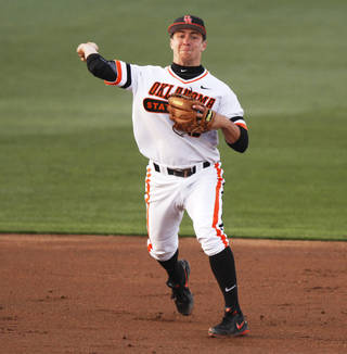 Oklahoma State's Donnie Walton (5) throws the ballk to first base during an NCAA college baseball game between Oklahoma State University (OSU) and Texas Christian University (TCU) at Allie P. Reynolds stadium in Stillwater, Okla., Friday, March 28, 2014. The series is the Cowboys' Big 12 home opener in the 2014 season. Photo by KT King, The Oklahoman