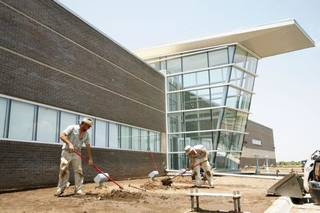 Larry Farnsworth and Cole Athay of Design Plus work on landscaping Monday at the Thunder's new practice facility. The team should be able to move into the building by August. ZACH GRAY - The Oklahoman