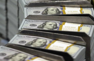 Freshly-cut stacks of $100 bills make their way down the line at the Bureau of Engraving and Printing Western Currency Facility in Fort Worth, Texas. AP File Photo LM Otero - AP