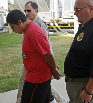 Raymond Harjo Jr. is led into the Pottawattamie County Court house in Shawnee on Wednesday, after an warrant had been issued for him in connection with the stabbing of 32-year-old Ronald Boley. Photo by Bryan Terry, The Oklahoman BRYAN TERRY - THE OKLAHOMAN