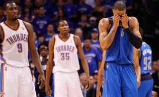 Dallas Mavericks' Tyson Chandler, right, front, wipes his face as Oklahoma City Thunder's Serge Ibaka (9) of Republic of Congo and Kevin Durant (35) walk up the court in the second half of Game 4 of the NBA Western Conference finals basketball series Monday, May 23, 2011, in Oklahoma City. (AP Photo/Eric Gay)