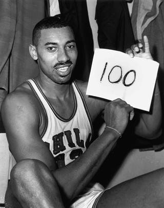 "In this March 2, 1962 file photo, Wilt Chamberlain of the Philadelphia Warriors holds a sign reading ""100"" in the dressing room in Hershey, Pa., after he scored 100 points, as the Warriors defeated the New York Knickerbockers 169-147. For 50 years, Chamberlain's 100-point night has stood as one of sports magic numbers. (AP Photo/Paul Vathis, File)"