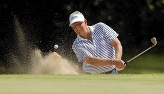 Colin Montgomerie hits out of a bunker on No. 13 during the third round of the U.S. Senior Open golf tournament at Oak Tree National in Edmond, Okla., Saturday, July 12, 2014. Photo by Nate Billings, The Oklahoman