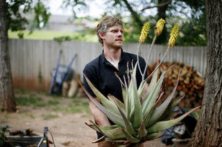 Daniel Meunier carries an Aloe Vera plant given to him by a client. Photo by Bryan Terry, The Oklahoman Bryan Terry - THE OKLAHOMAN