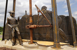 """Edmond's newest public art piece, """"West Edmond Oil Field,"""" depicts two men working in the oil field. The bronze statue is on display outside the Mitch Park YMCA and Edmond Competitive Pool, located in J.L. Mitch Park. PHOTO BY JIM BECKEL, THE OKLAHOMAN Jim Beckel"""