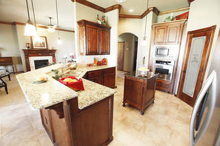 The model home's kitchen is finished in deep, rich-toned hardwood cabinetry. PAUL B. SOUTHERLAND - The Oklahoman