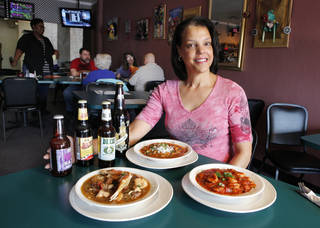 Thais Goodwin with bowls of seafood gumbo, crawfish etouffee, and shrimp creole prepared at the Bayou Grill and Bakery in Edmond. PAUL B. SOUTHERLAND - THE OKLAHOMAN