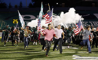Students lead the Edmond Santa Fe Wolves as they take the field before a high school football game between Edmond Santa Fe and Norman at Wantland Stadium in Edmond. Photo by Nate Billings, The Oklahoman Archives NATE BILLINGS -
