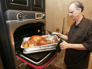 Claude Rappaport removes a turkey from his TurboChef oven after cooking for 39 minutes at his store, Culinary Kitchen. Claude, Lindy and Lori Rappaport, with help from their friend Clayton Bahr, will be cooking as many as 100 turkeys using the latest technology. Photo By Paul Hellstern, The Oklahoman