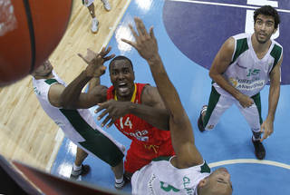 Serge Ibaka, centre left, of Spain is challenged by Joao Santos, right, from Portugal during the EuroBasket 2011, European Basketball Championships group A match between Spain and Portugal in Panevezys, Lithuania, on Thursday, Sept. 1, 2011. (AP Photo/Mindaugas Kulbis) ORG XMIT: XMK112