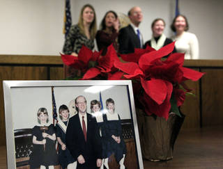 An old family photo is pictured in the foreground as Corporation Commissioner Bob Anthony poses with his daughters Thursday following his swearing-in at the Jim Thorpe Building in Oklahoma City. Photos by Sarah Phipps, The Oklahoman