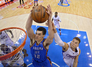 Oklahoma City Thunder center Steven Adams (12) grabs a rebound along with Los Angeles Clippers forward Blake Griffin, right, in the second half of Game 3 of the Western Conference semifinal NBA basketball playoff series, Friday, May 9, 2014, in Los Angeles. The Thunder won 118-112. (AP Photo/Mark J. Terrill)