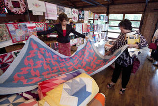 Quilt historian Judy Howard, left, shows Cheryl DeLay a quilt at a Mission Norman fundraiser. Quilts were donated for the sale, with proceeds going toward the agency's efforts to feed the hungry. PHOTO BY STEVE SISNEY, THE OKLAHOMAN