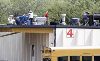 Workers make repairs to a hail damaged roof recently at the Oklahoma City Public Schools service center in northeast Oklahoma City. Hailstorms in 2010 and 2012 damaged dozens of buildings throughout the school district. Photo by Steve Gooch, The Oklahoman Steve Gooch