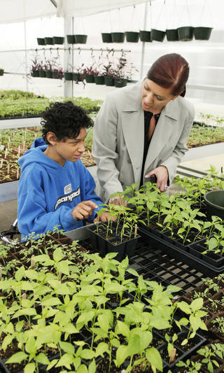 Seventh-grader Ivan Morgan, 13, talks Tuesday with principal Aspasia Carlson about plants being grown by the horticulture class in the greenhouse for a plant sale at John Marshall Mid-High School. Photo by Paul B. Southerland, The Oklahoman