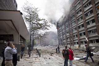 Smoke pours from a building in the centre of Oslo, Friday July 22, 2011, following an explosion that tore open several buildings including the prime minister's office, shattering windows and covering the street with documents.(AP Photo/Thomas Winje