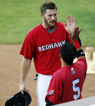 RedHawks outfielder Robbie Grossman, back, extended the Pacific Coast League's longest hitting streak to 18 games on Monday. Photo by KT King/The Oklahoman