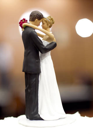 A figurine of a bride and a groom sits atop a wedding cake. AP Photo