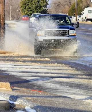 Vehicles try to navigate through ice and water from a water main break at the intersection of NW 50 Street and Portland Ave. in Oklahoma City Tuesday, Feb. 11, 2014. Photo by Paul B. Southerland, The Oklahoman