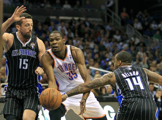 Oklahoma City Thunder's Kevin Durant (35) loses control of the ball as he tries to get between Orlando Magic's Hedo Turkoglu (15) and Jameer Nelson (14) during the first half of an NBA basketball game on Thursday, March 1, 2012, in Orlando, Fla. (AP Photo/John Raoux) ORG XMIT: DOA101