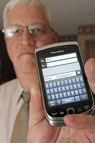 David Tucker, executive director of Vermont's Enhanced 911 Board, holds a smart phone in Montpelier, Vt. AP File Photo Toby Talbot -