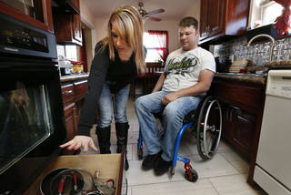 Jean Pittman and her husband, EH, show off their remodeled and handicap-accessible kitchen. The work was completed after he was injured in the May 20 Moore tornado. PHOTO STEVE SISSNEY, THE OKLAHOMAN. STEVE SISNEY - THE OKLAHOMAN