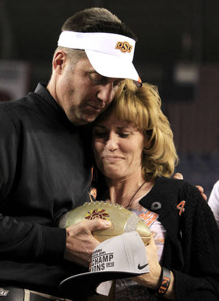 Oklahoma State head coach Mike Gundy, left, hugs Shelley Budke, wife of former Oklahoma State women's basketball coach Kurt Budke who died in a plane crash in 2011, as Gundy presents the Fiesta Bowl Championship Trophy to her after the Fiesta Bowl NCAA college football game Monday, Jan. 2, 2012, in Glendale, Ariz. Oklahoma State defeated Stanford 41-38 in overtime.(AP Photo/Ross D. Franklin) ORG XMIT: PNP152