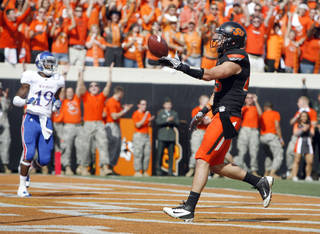 Oklahoma State's Josh Cooper (25) celebrates a touchdown in front of Kansas' Isiah Barfield (19) during the first half of the college football game between the Oklahoma State University Cowboys (OSU) and the University of Kansas Jayhawks (KU) at Boone Pickens Stadium in Stillwater, Okla., Saturday, Oct. 8, 2011. Photo by Sarah Phipps, The Oklahoman