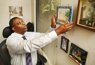 Clyde Wafford places a framed drawing done by his oldest son back on a wall next to his desk after taking it down to show to a visitor in his office. Wafford is founder and president of OrionNet Systems LLC. His company produces and sells practice management software for counseling centers in Oklahoma. He was photographed in his Oklahoma City office on Monday, Aug. 9, 2013. Photo by Jim Beckel, The Oklahoman.