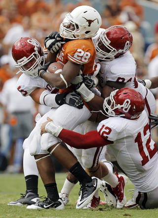 UT's Malcolm Brown (28) is taken down by, clockwise from left, Jaydan Bird (55), Frank Alexander (84) and Travis Lewis (12) in the second half during the Red River Rivalry college football game between the University of Oklahoma Sooners (OU) and the University of Texas Longhorns (UT) at the Cotton Bowl in Dallas, Friday, Oct. 7, 2011. OU won, 55-17. Photo by Nate Billings, The Oklahoman
