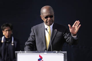 "Republican presidential candidate Herman Cain announces he is suspending his campaign as his wife Gloria, left, looks on Saturday, Dec. 3, 2011, in Atlanta. ""I am suspending my presidential campaign because of the continued distractions and the continued hurt caused on me and my family,"" Cain told several hundred supporters gathered at what was to have been the opening of his national campaign headquarters. (AP Photo/David Tulis) ORG XMIT: GADT103"