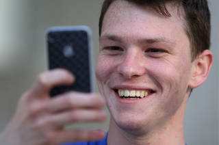 Jeremiah Ulibarri checks out his iPhone 4 June 24 outside of an Apple store in Chicago. AP Photo