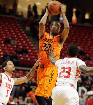 Oklahoma State's Markel Brown, center, passes under pressure from Texas Tech's Josh Gray (5) and Jamal Williams Jr., (23) during their NCAA college basketball game, Wednesday, Feb. 13, 2013, in Lubbock, Texas. (AP Photo/The Avalanche-Journal, Zach Long) ALL LOCAL TV OUT ORG XMIT: TXLUB101