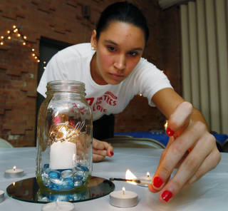 "Molly Retherford lights candles on tables at the OU Hillel Foundation's annual ""Latkas for Love"" fundraiser oin Norman. STEVE SISNEY - THE OKLAHOMAN"