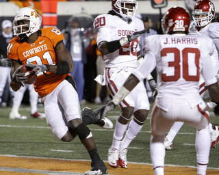 Oklahoma State's Justin Blackmon (81) scores a touchdown in front of Oklahoma's Quinton Carter (20) and Javon Harris (30) during the Bedlam college football game between the University of Oklahoma Sooners (OU) and the Oklahoma State University Cowboys (OSU) at Boone Pickens Stadium in Stillwater, Okla., Saturday, Nov. 27, 2010. Photo by Chris Landsberger, The Oklahoman