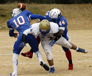 Hobart's Aaron Hernandez fumbles the ball out of bounds on the hit from Alfonzo McMillian (10 and Larry Lambeth (44) as Millwood plays Hobart in high school football playoff action on Saturday, Nov. 23, 2013, in Oklahoma City, Okla. Photo by Steve Sisney, The Oklahoman