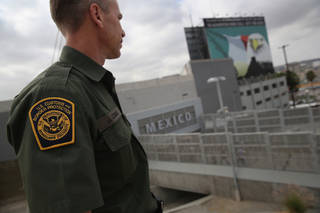 """SAN YSIDRO, CA - OCTOBER 03: U.S. Border Patrol agent Jerry Conlin stands on the American side of the U.S.-Mexico border on October 3, 2013 at the San Ysidro port of enty into Mexico, California. While hundreds of thousands of government workers were furloughed due to the federal shutdown, thousands of Border Patrol agents, air-traffic controllers, prison guards and other federal employees deemed """"essential"""" remain on duty, although their pay may be delayed. (Photo by John Moore/Getty Images)"""