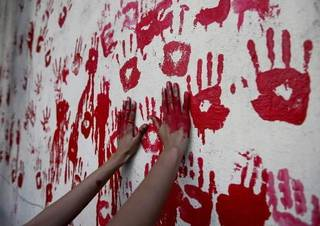 Students paint a wall with hand prints in a tribute to last year's terror attack victims in Mumbai, India, Wednesday, Nov.25, 2009. 10 militants with assault rifles fanned out across Mumbai last Nov. 26, attacking a train station, hotels, and other targets, paralyzing India's financial capital and shocking the country killing 166 people. (AP Photo)