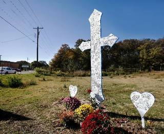 Family and friends recently placed a large white cross as a memorial to Carina Saunders, 19, in a field on the north side of NW 23 Street west of Rockwell Avenue in Bethany. Saunders' dismembered body was found in a duffel bag in a field next to a national chain grocery store on Oct. 13. Police continue to search for her killer. This photo taken Thursday, Nov. 3, 2011. Photo by Jim Beckel
