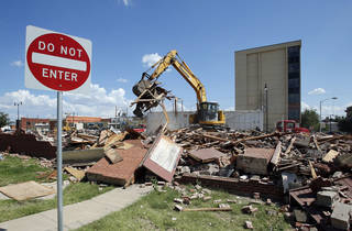 A wrecking crew takes down a city-owned building at Gray Street and Peters Avenue in Norman. PHOTOS BY STEVE SISNEY, THE OKLAHOMAN