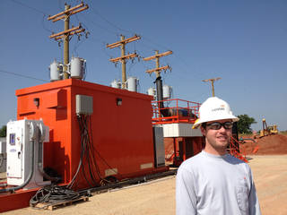 Jarod Tracy, production engineer for Devon Energy Corp., stands in front of a prototype General Electric generator southwest of Stillwater. The generator runs on natural gas in a part of northern Oklahoma's Mississippian oil play where utility power is not available. - provided