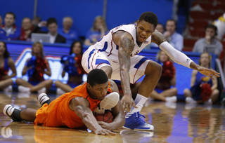 Oklahoma State guard Marcus Smart, left, gathers a loose ball ahead of Kansas guard Ben McLemore during the second half of an NCAA college basketball game in Lawrence, Kan., Saturday, Feb. 2, 2013. Oklahoma State won 85-80. (AP Photo/Orlin Wagner) ORG XMIT: KSOW118