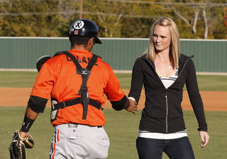 Sarah Harper, right, the girlfriend of slain Australian baseball player Chris Lane, takes the ball from East Central University catcher Andrew Ayrado, left, after throwing out the ceremonial first pitch before a game between two of his former teams, Redlands Community College and East Central University, held in Lane's memory in Duncan, Okla, Thursday, Oct. 24, 2013. (AP Photo/Sue Ogrocki)