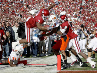 OU's DeMarco Murray scores a touchdown in front of OSU's Donald Booker, at left, Terrance Anderson and Markelle Martin and OU's Jaz Reynolds during the first half of the Bedlam college football game between the University of Oklahoma Sooners (OU) and the Oklahoma State University Cowboys (OSU) at the Gaylord Family-Oklahoma Memorial Stadium. AP Photo